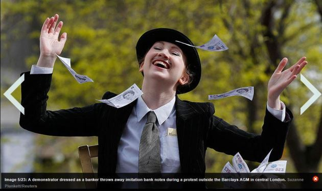 Demonstrator before Barclays Bank in central Lodon dressed as banker throwing away paper money bills.