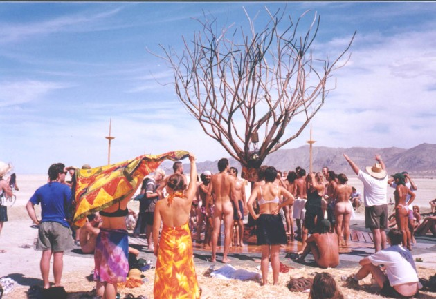 Copper tree with people gathered around getting the water relief