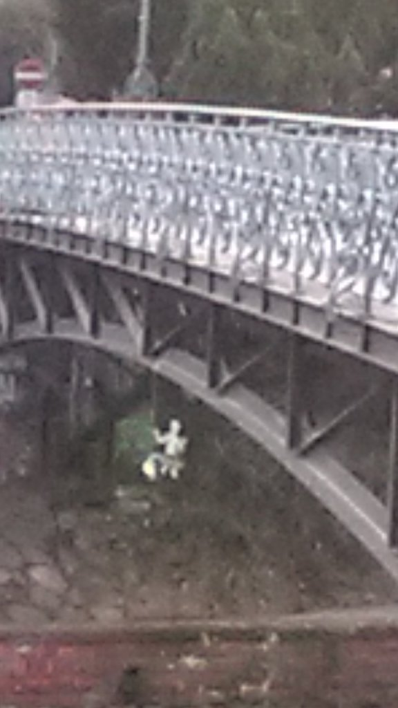 miniature puppet swinging beneath bridge